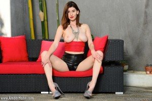 Amber Hahn in black leather shorts and red top